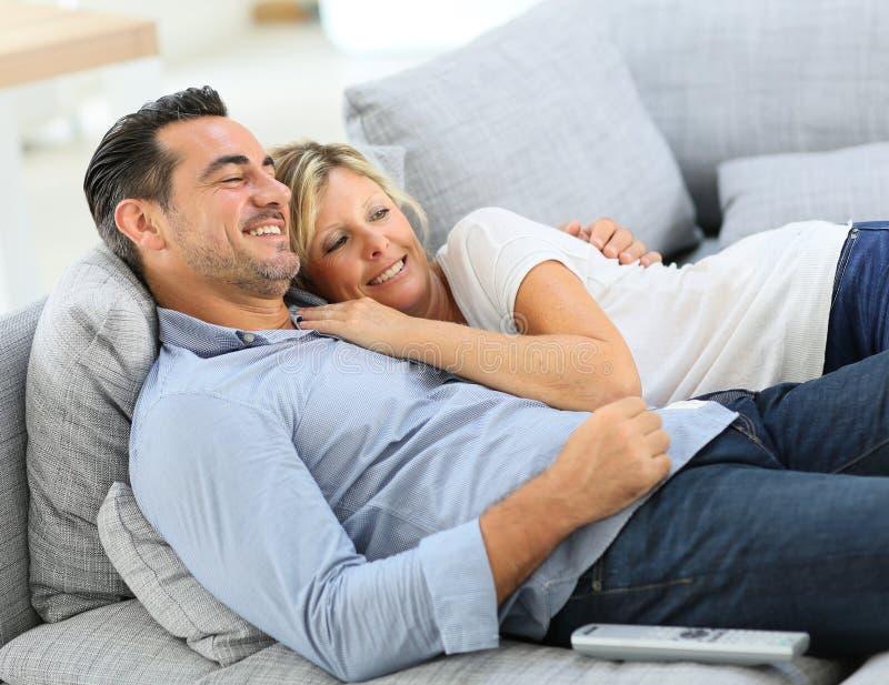 Medelåldersa par som tycker om hålla ögonen på tv royaltyfri bild