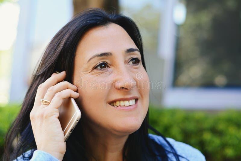 Medelåldrig kvinna som talar på telefonen royaltyfria foton