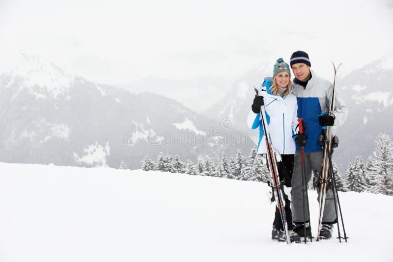 Medelåldriga par skidar på ferie i berg royaltyfri fotografi