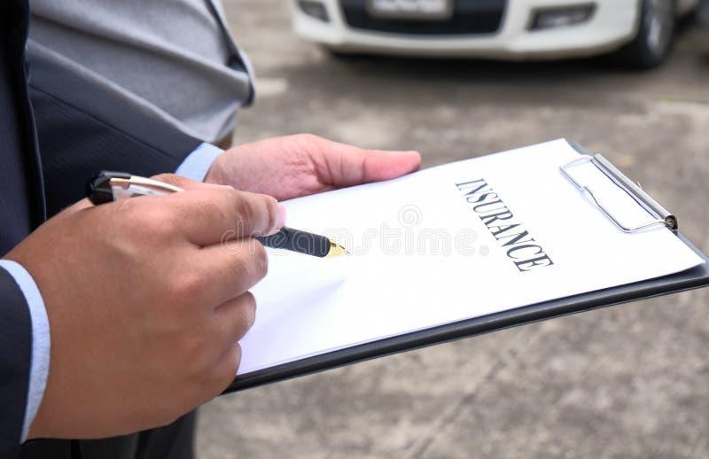 Medel för försäkring för förlustregulator Inspecting Damaged Car royaltyfri bild