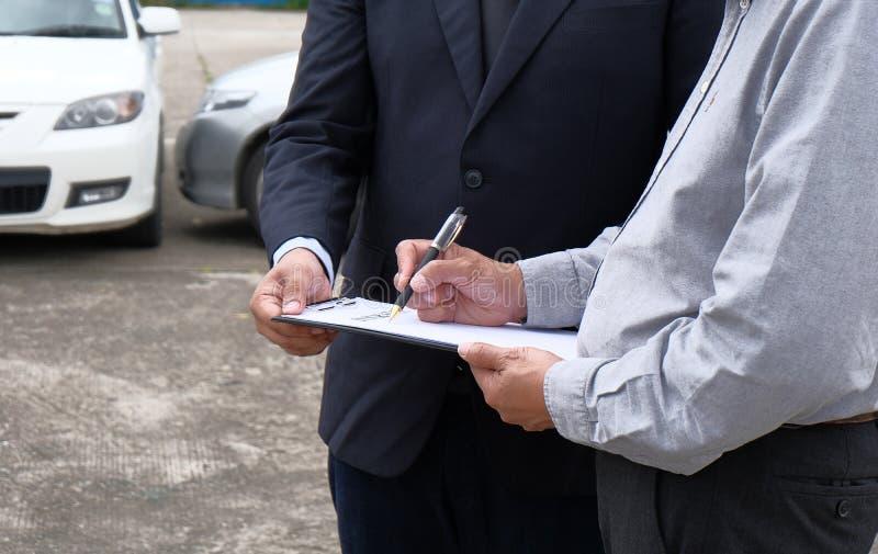 Medel för försäkring för förlustregulator Inspecting Damaged Car arkivfoto