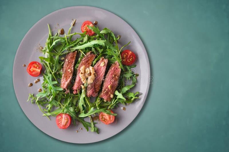 Medel för nötköttbiff, Ruccola sallad med tomater och valnötter, grå färgplatta royaltyfria foton