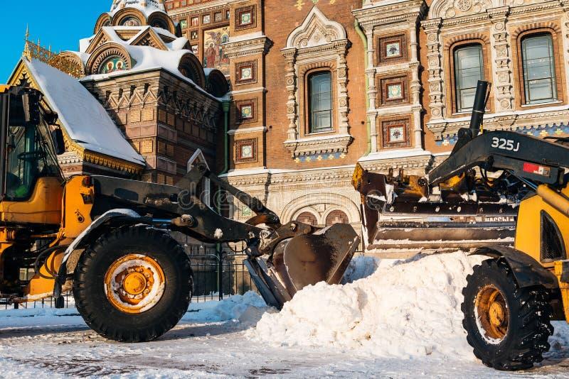 Medel för snöborttagning som tar bort snö Traktoren gör klar vägen efter tungt snöfall i St Petersburg, Ryssland royaltyfria foton