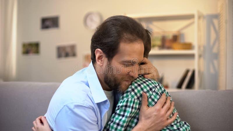 Medel?lders fader som kramar skolpojkesonen, familjomsorg och f?rtroendefull f?rbindelse arkivfoto