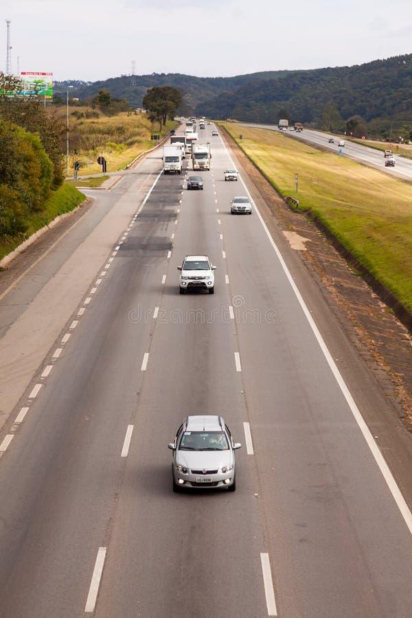 Medel på huvudvägen BR-374 med billyktor på under dagsljuset som lyder de nya brasilianska transportlagarna arkivfoto