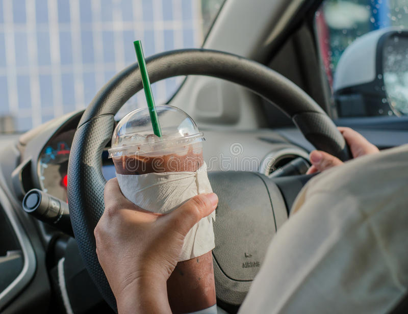 Medelbegreppet - man att dricka kaffe, medan köra bilen royaltyfri foto