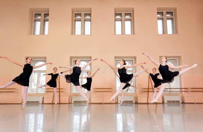 Medelgrupp av tonårs- flickor som öva klassisk balett i en stor dansa studio royaltyfria bilder