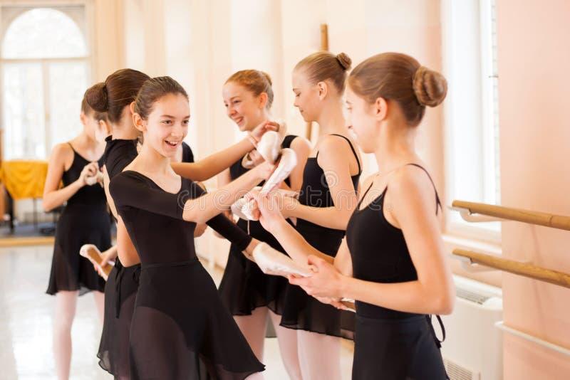 Medelgrupp av tonårs- flickor som har gyckel och kopplar av efter balettgrupp arkivfoton