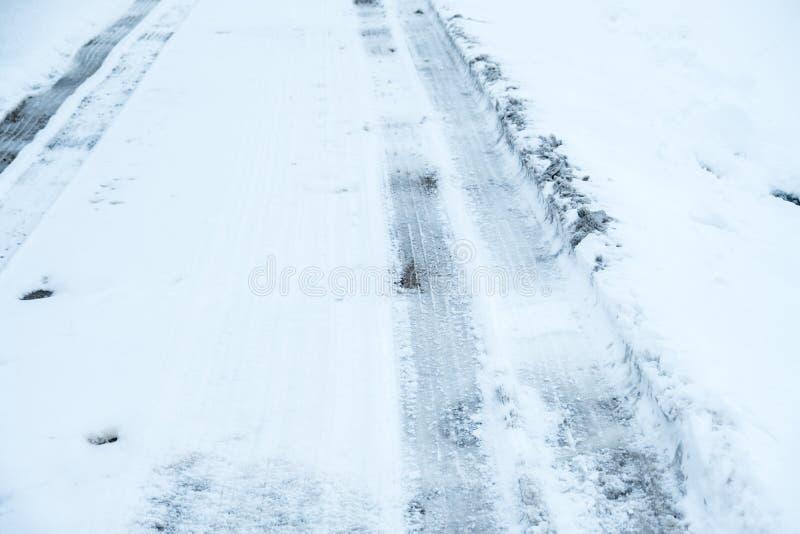 Medelgummihjulspår på vägen som täckas i snö och is tillstånd som kör vinter arkivbild