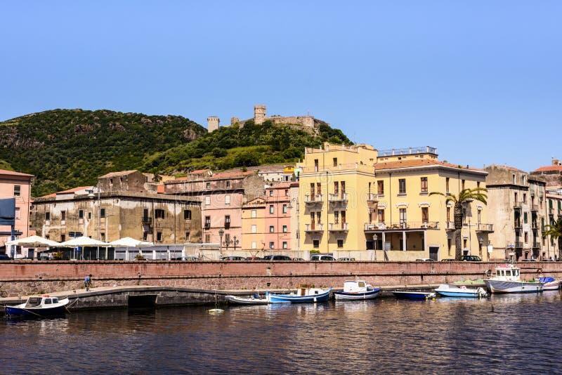Medelhavs- hus och Serravalle ` s rockerar på kusten av den Tremo floden i härliga Bosa, Sardinia, Italien royaltyfria foton