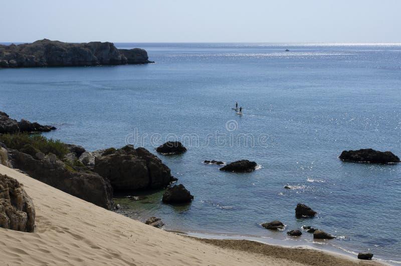 Medelhavs- kust med förlovad standup paddleboarding för oidentifierade turister fotografering för bildbyråer