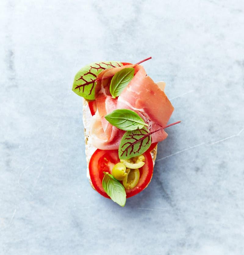 Medelhavs--stil öppen smörgås med Serrano skinka-, tomat-, Gren Olives, basilikasidor och röd syra arkivfoto