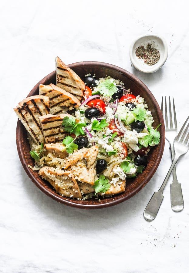 Medelhavs- stillunch - couscous, k?rsb?rsr?da tomater, gurkor, fetaost, oliv sallad och citron?rter grillade det fega br?stet arkivfoto