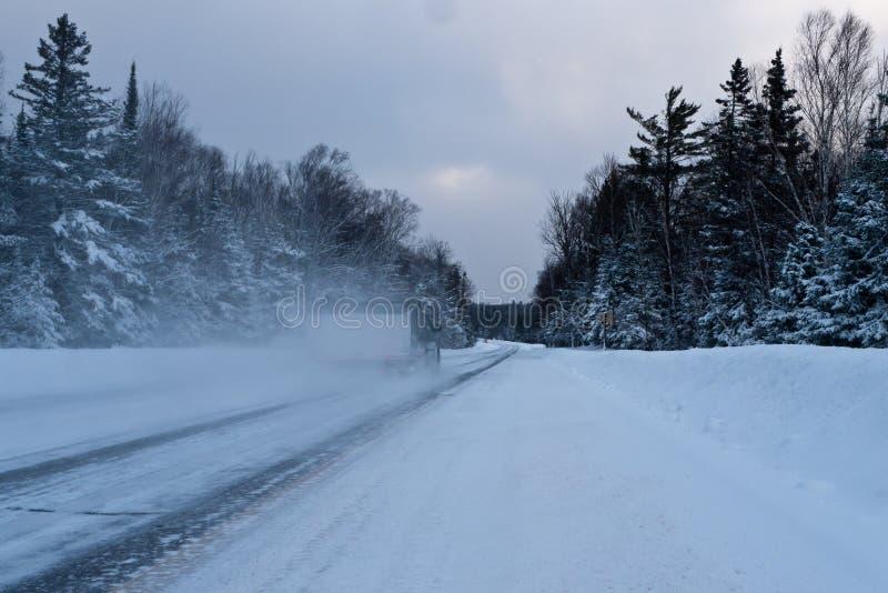 Medelkörning på den tomma ändlösa vägen till och med djupfryst landskap av Minnesota arkivfoto