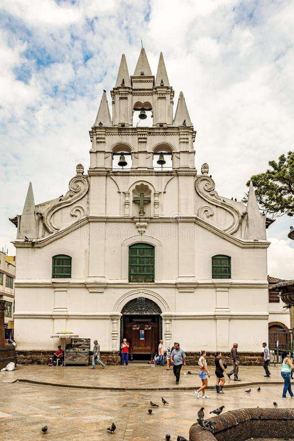 La Veracruz catholic church and the only colonial style church i. Medellin, Colombia, March 24, 2018: Locals and tourists walking by La Veracruz church and only stock photos