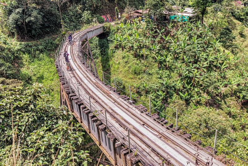 Old railroad track near Medellin, Colombia. Medellin, Colombia - March 25, 2018: People riding bicycle on old railroad track near Medellin. Crossing old bridge royalty free stock photos