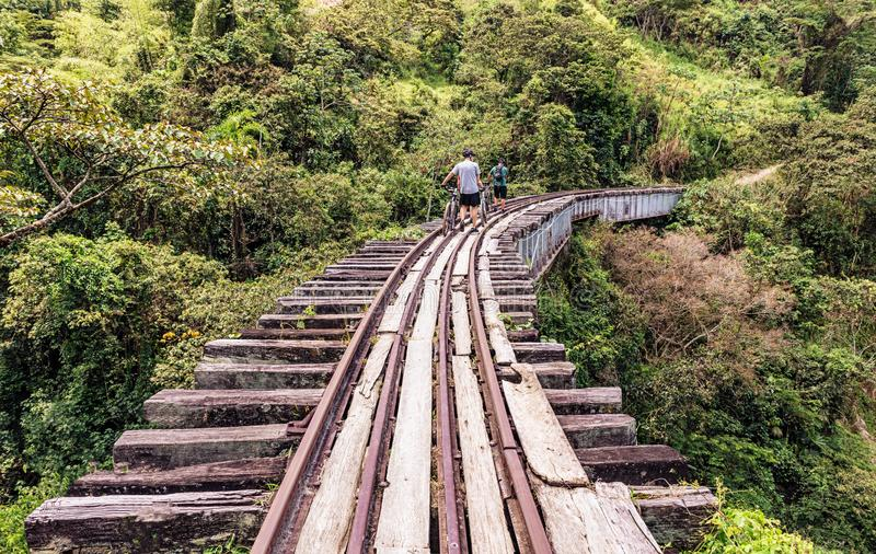 Old railroad track near Medellin, Colombia. Medellin, Colombia - March 25, 2018: People riding bicycle on old railroad track near Medellin. Crossing old bridge royalty free stock photo