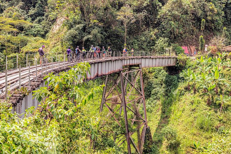 Old railroad track near Medellin, Colombia. Medellin, Colombia - March 25, 2018: People riding bicycle on old railroad track near Medellin. Crossing old bridge stock photos