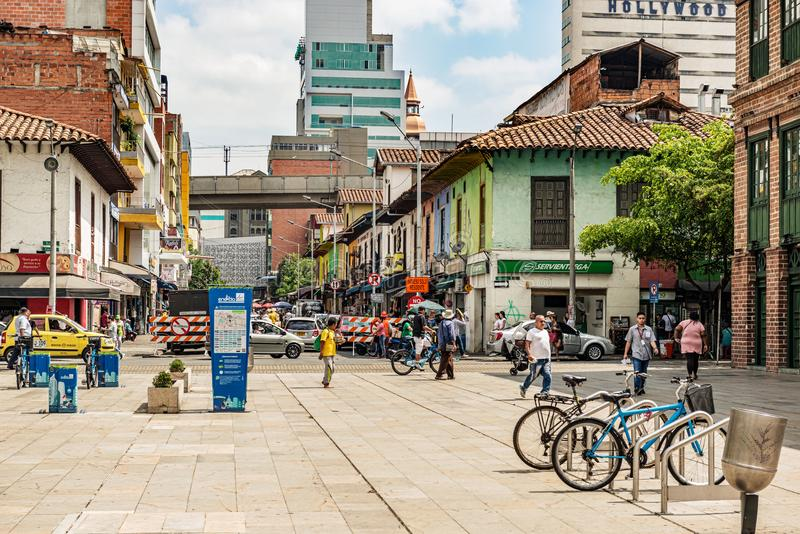Commercial street in Medellin, Colombia. Medellin, Colombia - March 26, 2018: People walking on the street with old colonial houses and shops in Medellin royalty free stock images