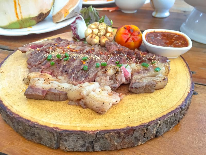 Medelrått skivat steknötkött med thai kryddig sås på trämaträtt royaltyfria bilder