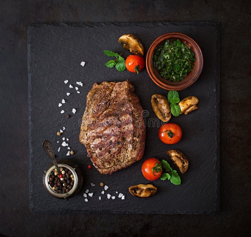 Medelsällsynt nötkött för saftig biff med kryddor och grillade grönsaker fotografering för bildbyråer