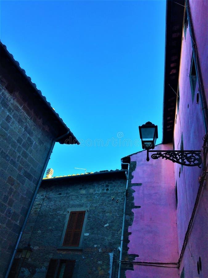 Medeltid konstruktion, gatalampa, rosa vägg och himmel i den Vitorchiano staden, Italien royaltyfria foton