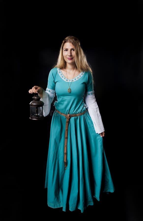 Medeltida flicka i turkosklänning med en tappninglampa arkivfoto