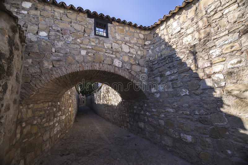 Medeltida grannskap i Baeza, bakgata med stenbågen, Jaen p arkivbilder