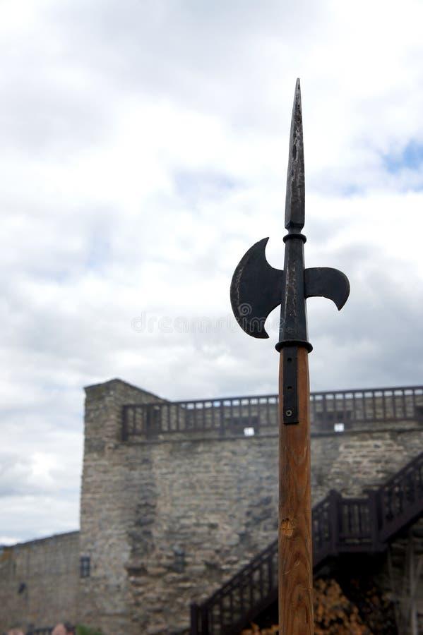 Medeltida halberdpike framme av bakgrunden för slottvägg och för molnig himmel arkivfoto
