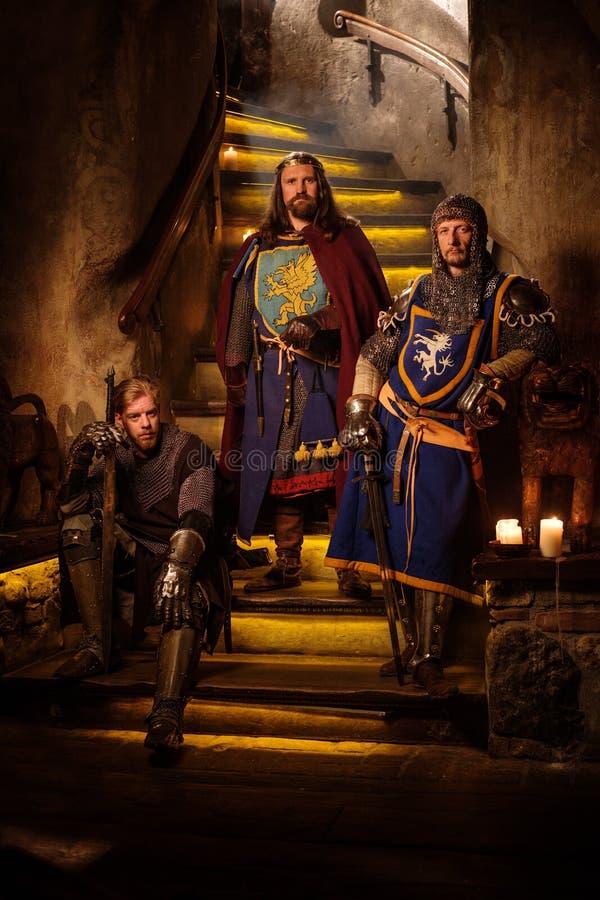 Medeltida konung med hans riddare i slottinre arkivfoto
