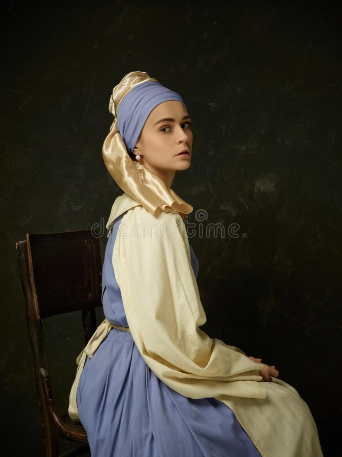 Medeltida kvinna i den historiska dräkten som bär den korsetterade klänningen och hättan arkivbilder
