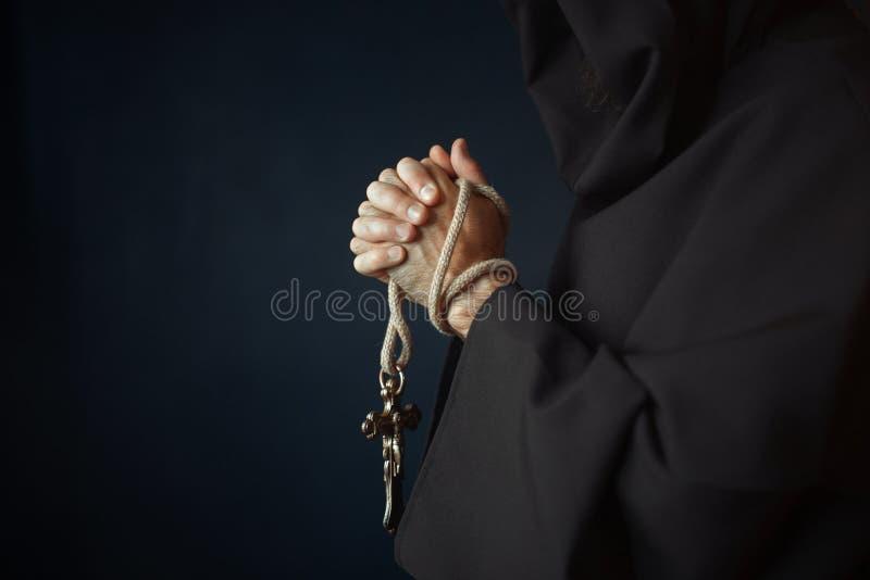 Medeltida munk som ber med träkorset i händer royaltyfri foto
