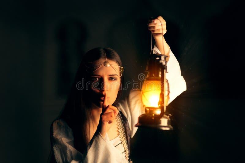 Medeltida prinsessa Holding Lantern och hålla en hemlighet royaltyfria foton