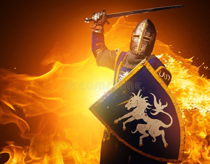 Medeltida riddare på brandbakgrund arkivfoton