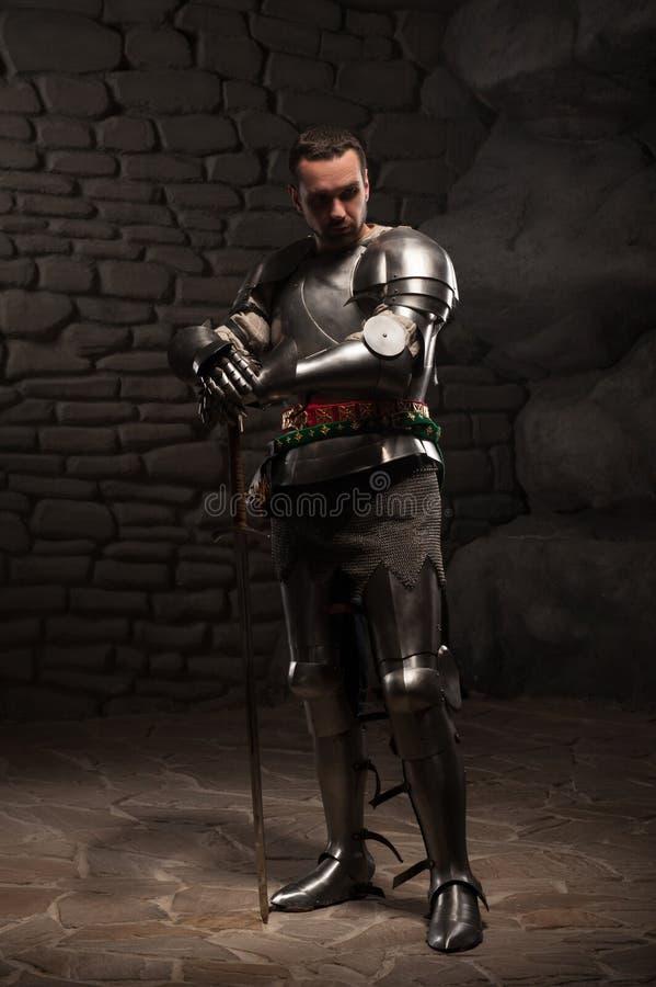 Medeltida riddare som poserar med svärdet i en mörk sten arkivfoto