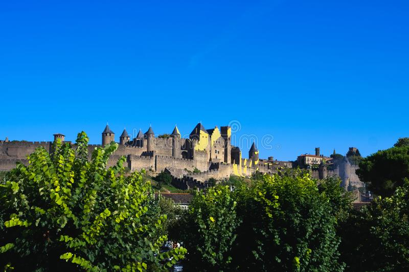 Medeltida stad av Carcassonne med det gula tecknet av Tour De France royaltyfri bild