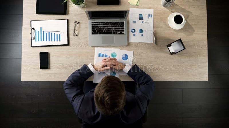Medewerker die de statistieken van het jarenbedrijf van laptop, archief, hoogste mening bekijken royalty-vrije stock foto
