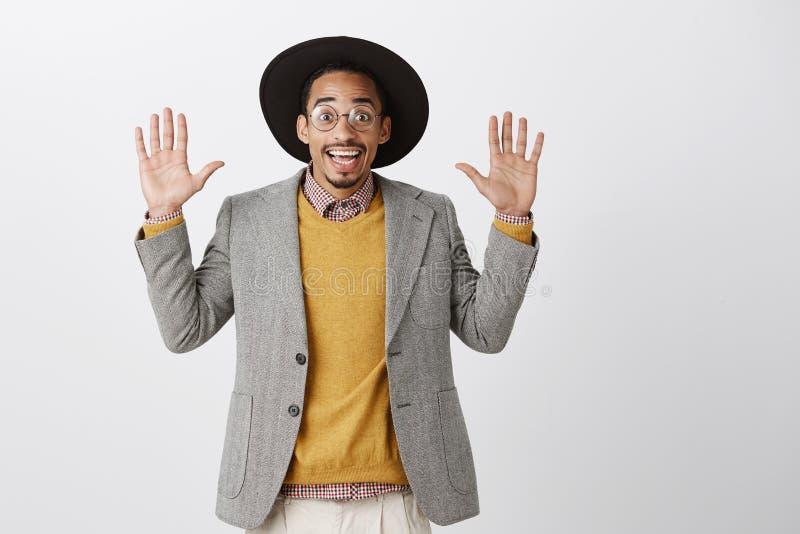 Medewerker die op stealing voedsel worden gevangen Portret van grappige knappe Afrikaanse kerel in in zwarte hoed en modieus stock foto's