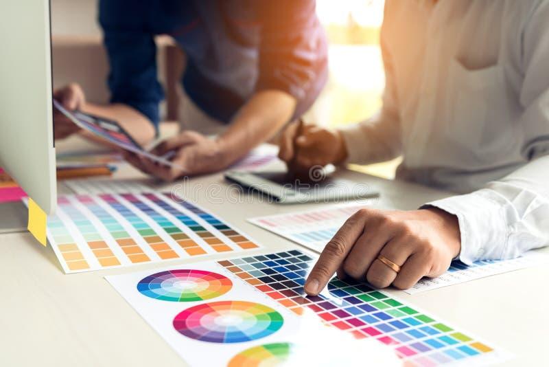 Medewerker grafische ontwerper die met vennootschap die kleur kiezen aan bureau in modern bureau werken stock afbeeldingen