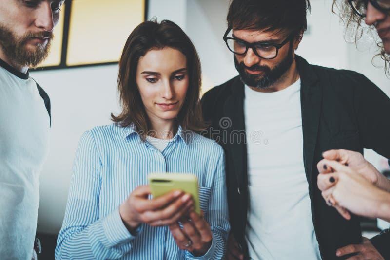 Medewerkers commercieel vergaderingsconcept Jong team die mobiel apparaat met behulp van op modern kantoor royalty-vrije stock afbeelding