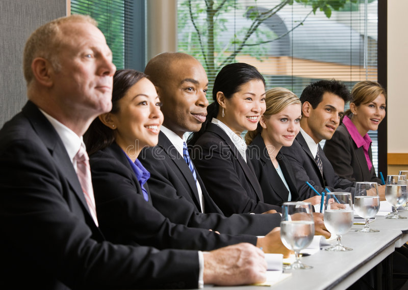 Medewerkers die bij lijst in conferentieruimte samenkomen stock foto's