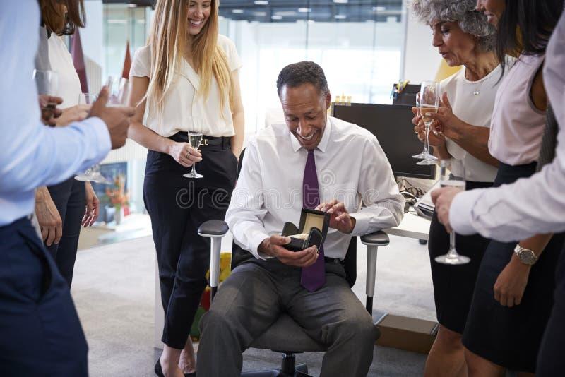 Medewerkers die een colleagueï¿ ½ s pensionering in het bureau vieren stock afbeelding