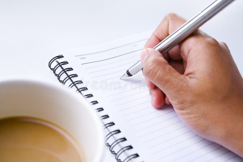 medföljd writing för bokkaffehand royaltyfri bild