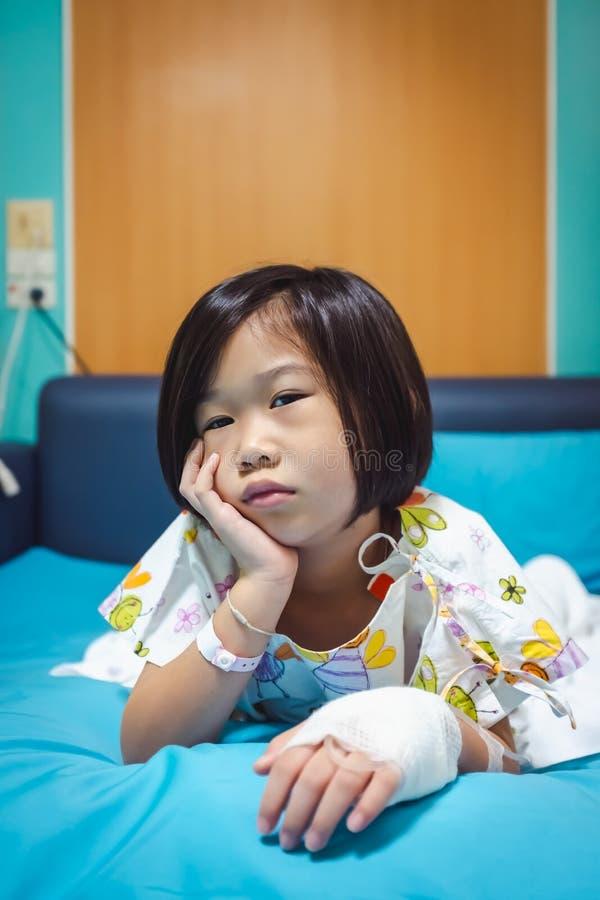 Medgav det asiatiska barnet f?r sjukdomen i sjukhus med salthaltig iv-droppande f?rest?ende H?lsov?rdber?ttelser royaltyfria foton