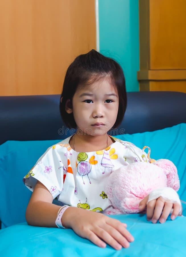 Medgav det asiatiska barnet f?r sjukdomen i sjukhus med salthaltig iv-droppande f?rest?ende royaltyfri foto