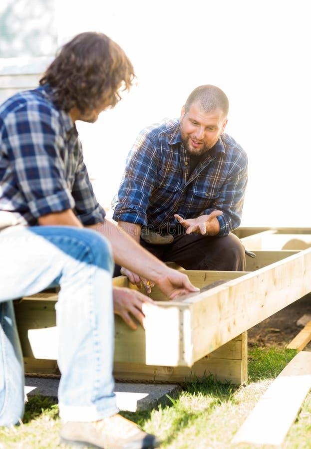 Medição de Communicating With Coworker do carpinteiro imagens de stock royalty free