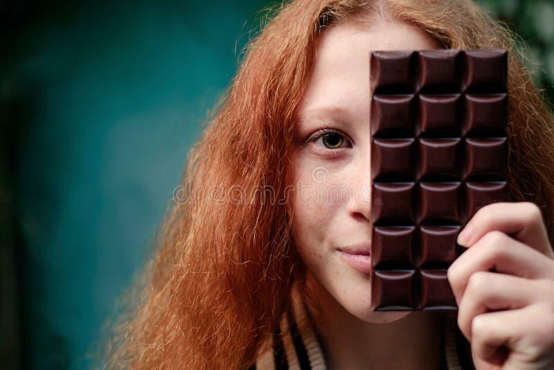 Media cara de la piel pelirroja de la muchacha sobre la barra de chocolate sabrosa imágenes de archivo libres de regalías