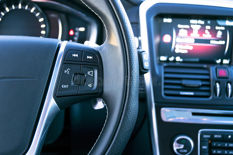 Media control buttons on the steering wheel in black leather with computer monitor, modern car interior.  royalty free stock images
