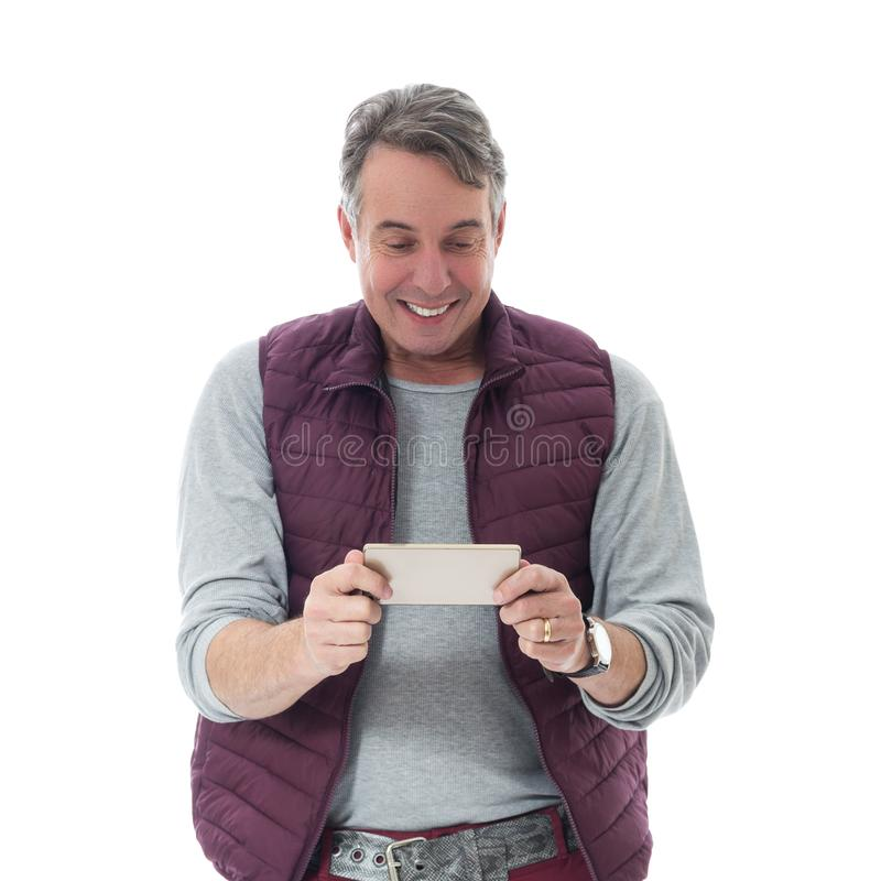 Media guardati uomo di mezza età sul cellulare Sta indossando un rosso immagine stock
