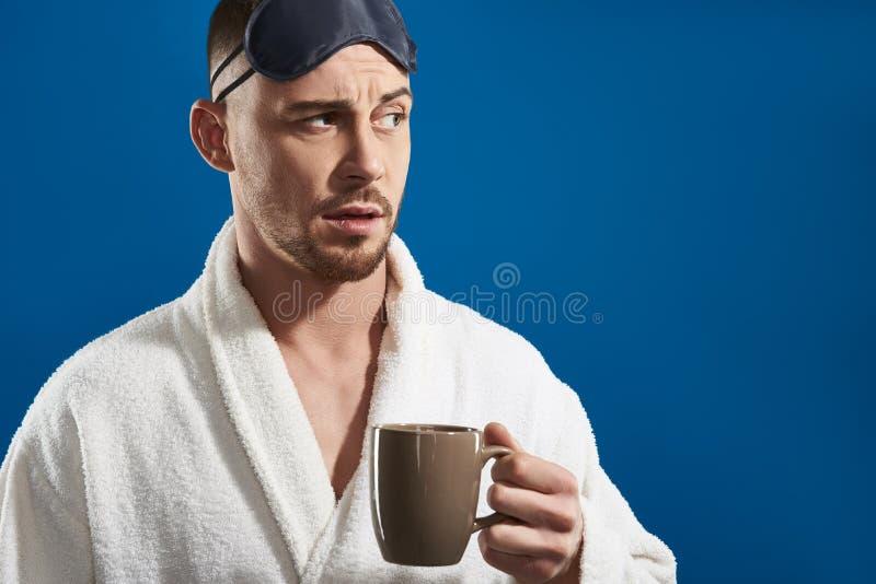 Media longitud del hombre hermoso joven que mantiene la taza con la bebida brazo fotos de archivo